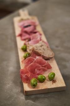 ミックスオリーブとパプリカの木製のまな板に生ハムの薄切りのクローズアップ