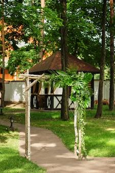 Свадебная арка украшена зелеными листьями на открытом воздухе свадебная церемония