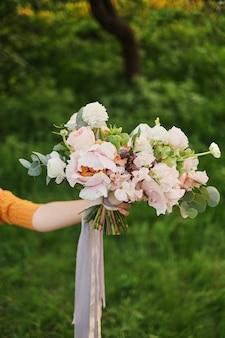 花嫁、デビッドオースティンローズ、緑の背景の手の中のウェディングブーケ