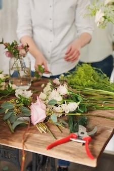 Руки флориста собирают свадебный букет. флорист на работе