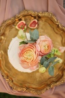 ラナンキュラスの花で飾られたピンクのケーキの配置