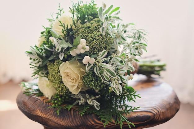 ブライダルブーケ。結婚式。白と緑の花のウェディングブーケは椅子の上に立つ