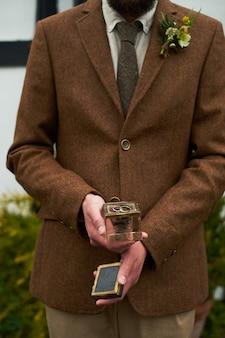文。リングとガラスのギフトボックスを保持している茶色のジャケットの男の手。