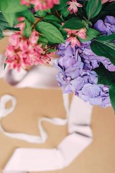 白い花、バラ、緑と椅子の上のリボンのウェディングブーケ