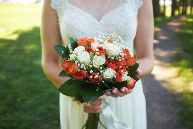 花嫁はオレンジ色のバラの花束を握る