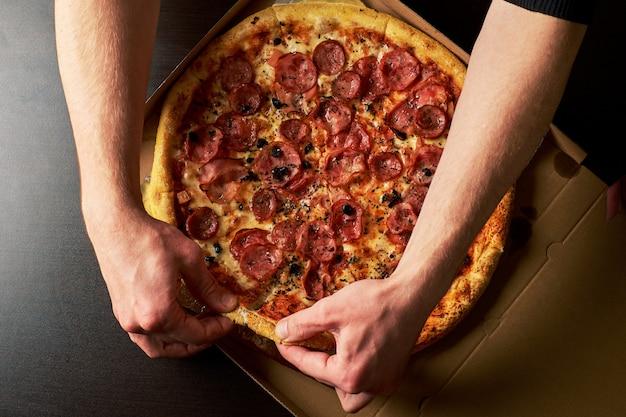 男の手は段ボール箱の暗いテーブルの背景に全体のピザからスライスチーズのピザを持っています。