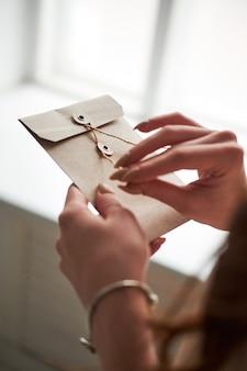 Женский женский рука держать конверт и открытку на деревянный стол, вид сверху