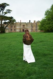 緑の野原を横切って逃げるファッション白いウェディングドレスの花嫁の全身像》