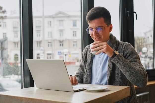 若い男は、ノートパソコンの後ろに働くカフェでフリーランサーです。男はコーヒーを飲みます。