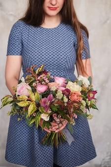 パステル調のカーネーションとユーカリの咲く花の花束を保持している女性の花屋