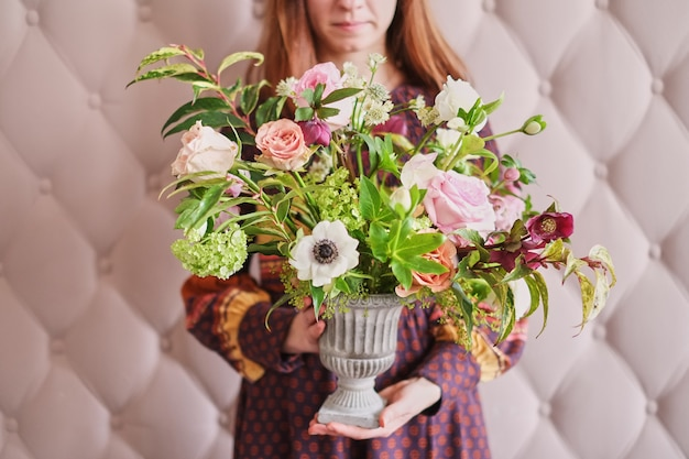 ピンクの壁に対してパステルカラーのカーネーションとユーカリの花束を持って若い女性の花屋。
