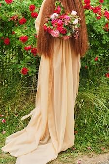 美しい大きなウェディングブーケを持ったシルクのウェディングドレスの花嫁