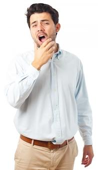 白い背景にあくびのジェスチャーで疲れた男