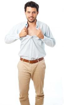 若い男がスーパーヒーローのように振る舞い、白い背景の上に彼のシャツを引き裂く