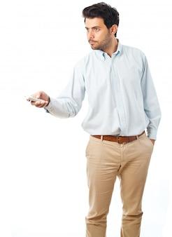 白い背景の上のリモコンで指している若い男
