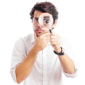 Молодой человек смотрит через увеличительное стекло