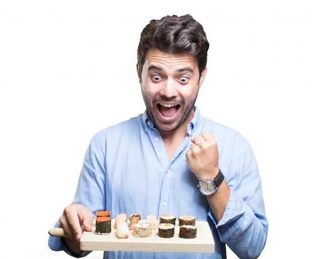 Молодой человек ест суши на белом фоне