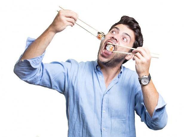 若い男が白い背景の上に寿司を食べる