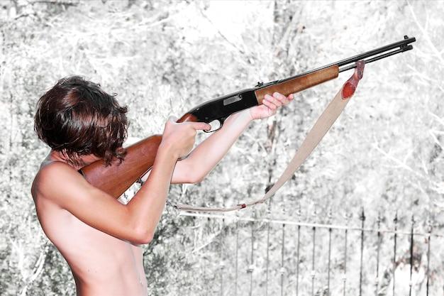 Мальчик целится из винтовки