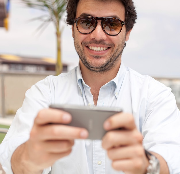 Счастливый молодой человек с мобильным телефоном