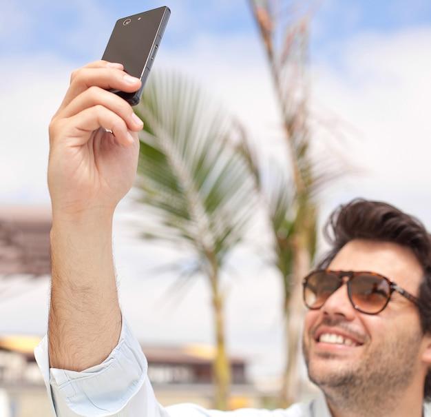 Молодой человек фотографирует с мобильного телефона
