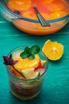 オレンジ、キウイ、グレープフルーツの青緑色の木製の背景からのフレッシュジュース。