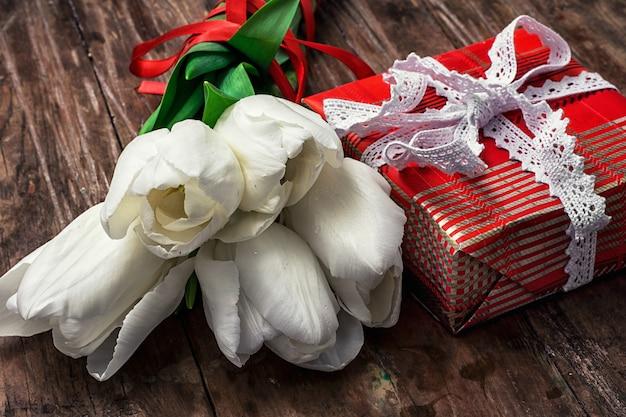 Упакованная подарочная коробка на фоне букета белых тюльпанов