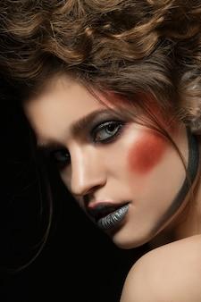 明るいメイクの女の子。赤銀のメイクアップとロマンチックな髪型と美しい女性モデルの魅力ポートレート。肌に光沢のある華麗なファッションハイライター、セクシーな艶のある唇、濃い眉毛