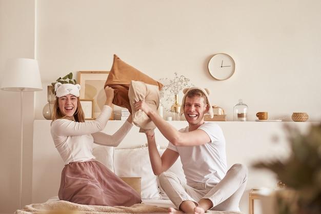 笑ってベッドで遊んで愛のペア。男と女は枕を戦う。若い幸せなカップルが自宅の寝室のベッドの枕を打つ