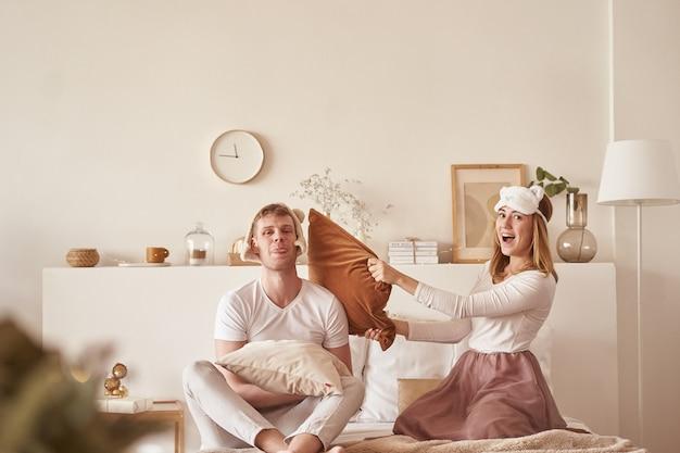 笑ってベッドで遊んで愛のペア。若い幸せなカップルが自宅の寝室のベッドの枕を打つ