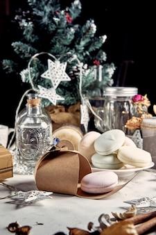 Рождественская открытка. зефир ручной работы лежит в подарочной коробке на фоне.