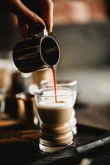 カフェでコーヒーを作るバリスタの手。牛乳と伝統的なエスプレッソのカップ。ショットグラスに注ぐコーヒー。トーン画像