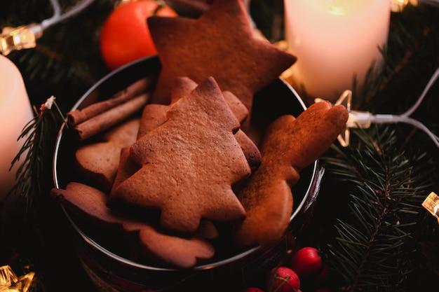 クリスマスパーティーのためのジンジャーブレッドクッキーと新年の花輪。フォーカスの束の上にクリスマスツリーケーキ。クローズアップ写真。