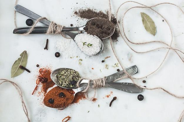 Специи в разных ложках на каменном мраморном столе. деревенская винтажная тонировка