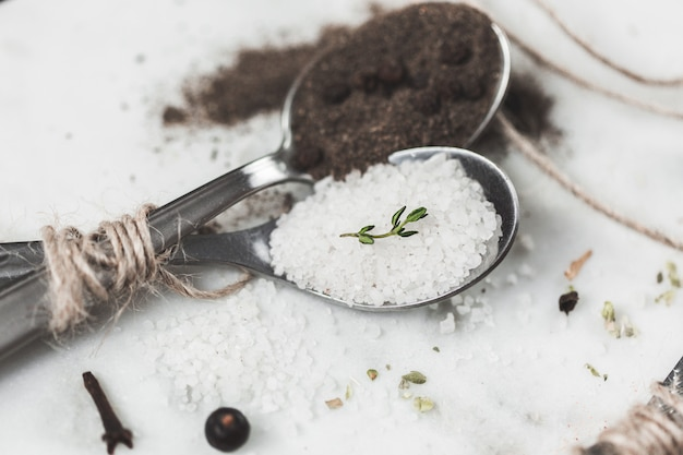Специи в ложках. соли и перца. камень мраморный стол. деревенская винтажная тонировка