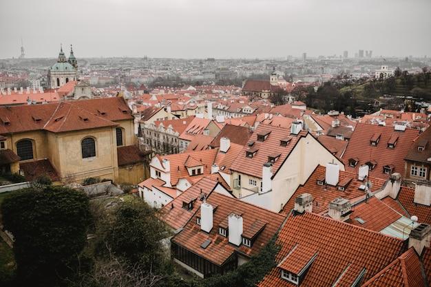 赤い屋根と教会とプラハのパノラマ。プラハ旧市街の街の眺め。素朴なグレーの色調