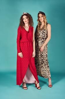 スタイリッシュな赤とヒョウのドレスを着た豪華な女性の屋内ファッションポートレートを閉じます。ターコイズブルーの壁に分離されたブロンドとブルネットの女の子。嬉しい巻き毛モデルの全身ショット