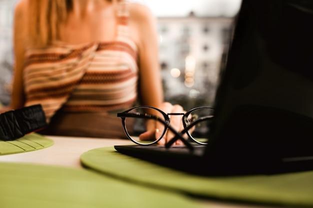 Девушка с ноутбуком. очки, лежа на ноутбуке на столе в кафе. фриланс работает в ресторане. бизнес фон