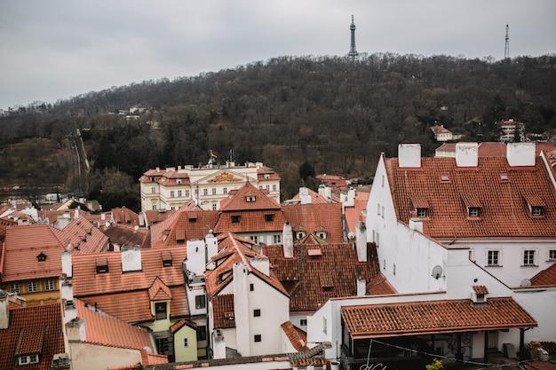 Панорама праги с красными крышами и церковью. вид на город из старого города прага. рустикальные оттенки серого цвета.