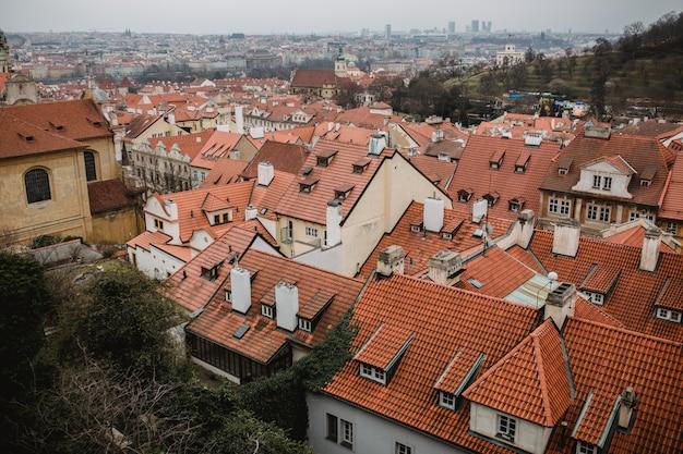 Город прага с красными крышами и церковь в тумане. вид на город из старого города прага. деревенская серая тонировка