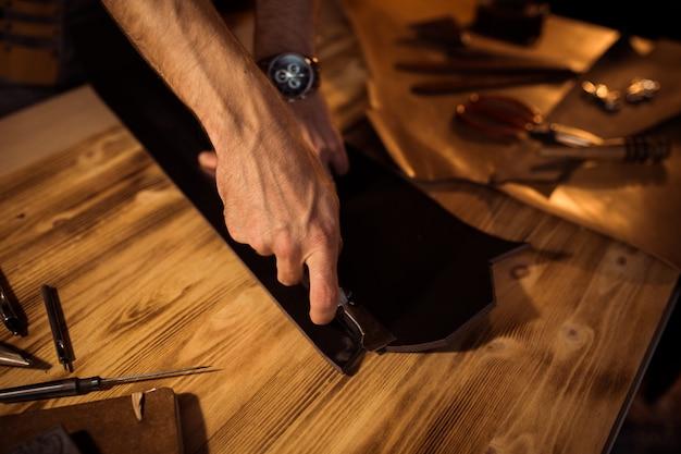 革工房での革ベルトの作業工程。クラフトツールを押しながら働く男。古いなめし工場のタナー。