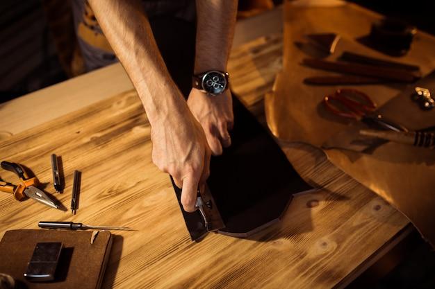革工房での革ベルトの作業工程。クラフトツールを押しながら働く男。古いなめし工場のタナー。木製のテーブルの背景。