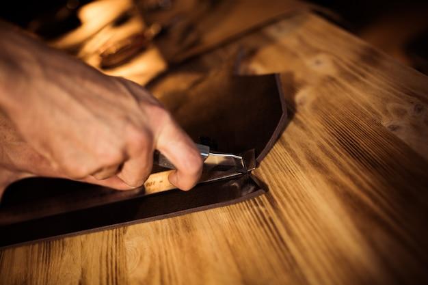 革工房での革ベルトの作業工程。クラフトツールを押しながら働く男。古いなめし工場のタナー。木製のテーブルの背景。男の腕を閉じる