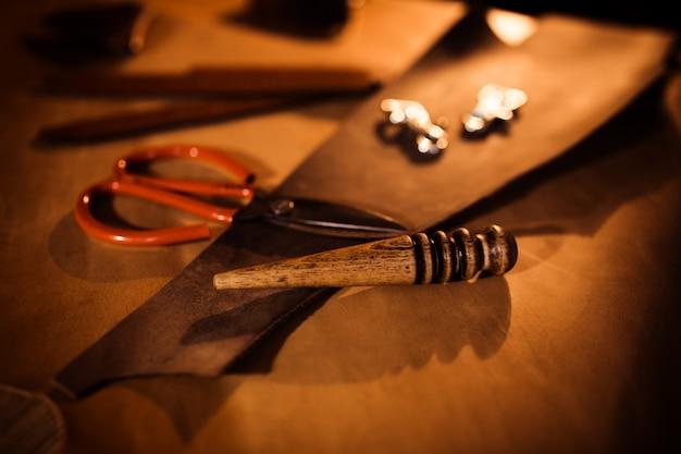 革工房での革ベルトの作業工程。古いなめし工場のタナー。木製のテーブルの背景にクラフトツール。