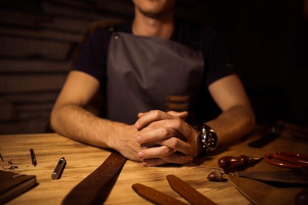 Рабочий процесс кожаного ремня в кожевенной мастерской. человек, держащий руки на деревянный стол. крафт инструменты на фоне. дубильщик в старом кожевенном заводе. закройте мужскую руку.