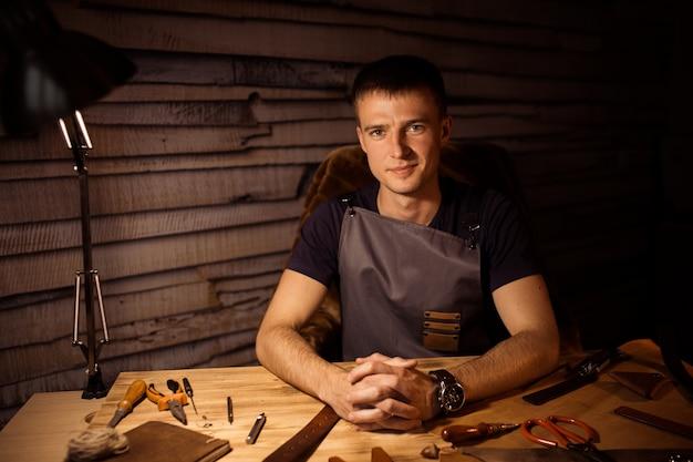 Рабочий процесс кожаного ремня в кожевенной мастерской. человек, держащий руки на деревянный стол. крафт инструменты на фоне. дубильщик в старом кожевенном заводе.