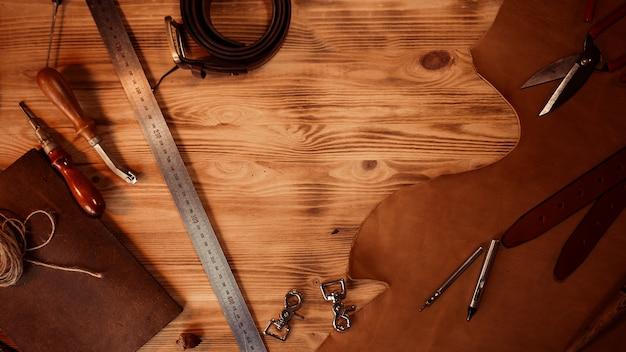 Кожаное ремесло. инструменты таннера на сером фоне деревянные вид сверху.