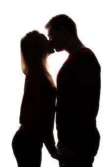 若いカップルがキスします。白い背景で隔離のシルエット。聖バレンタインデーのコンセプト