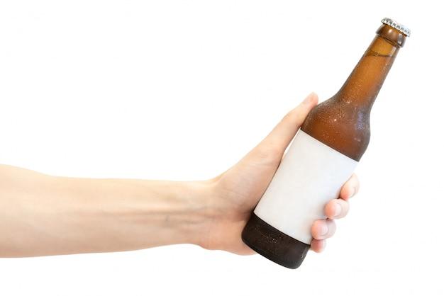 白で隔離される男性の手で白い空白のラベルが付いた茶色のガラスビール瓶