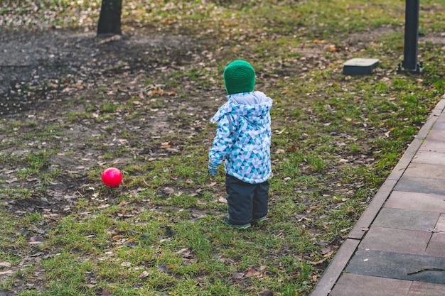 小さな子供は暖かく服を着て、公園で赤いボールで遊ぶ。